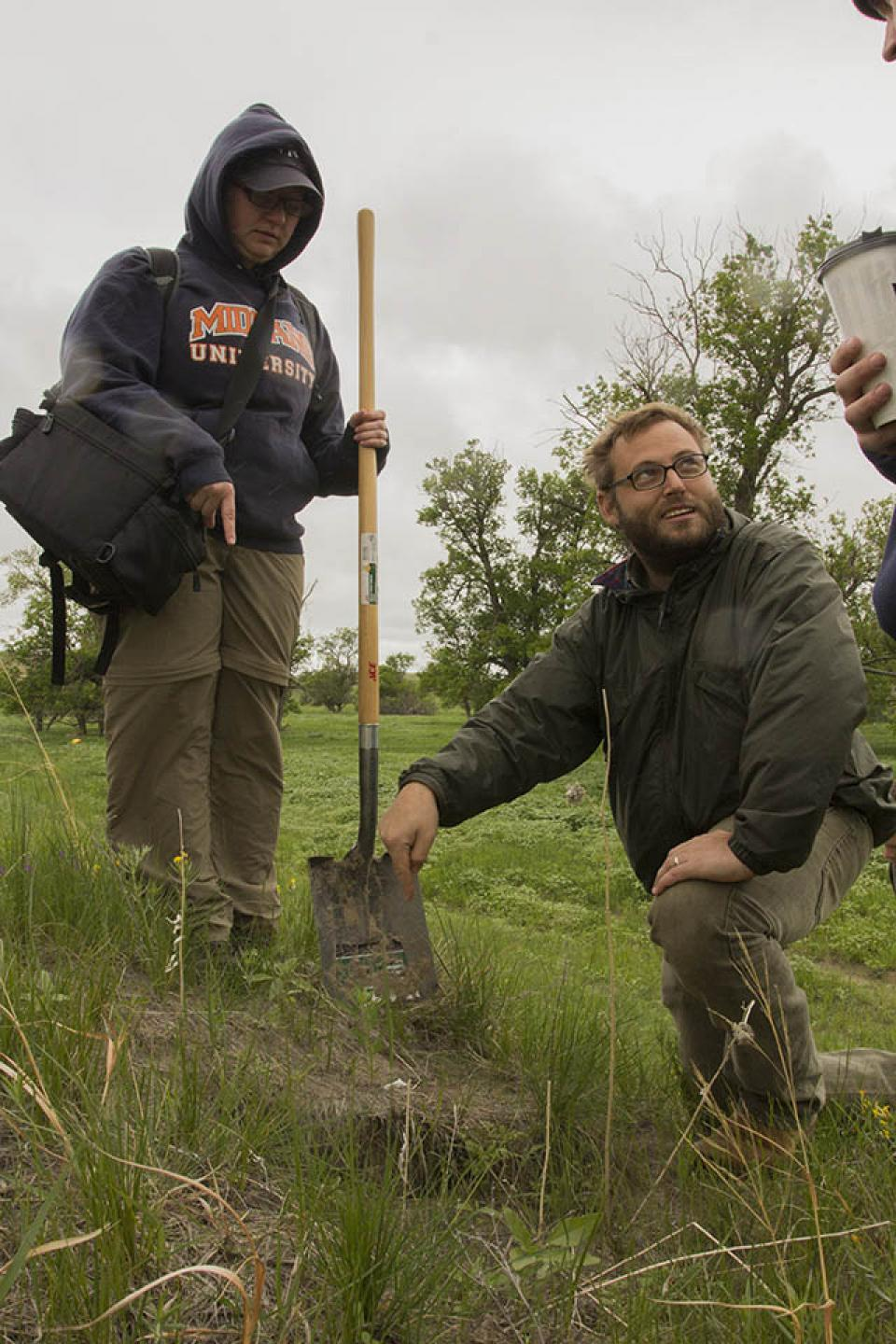 Professor Matthew Douglass and field school student Ty Hayes digging a test unit to take a soil sample.