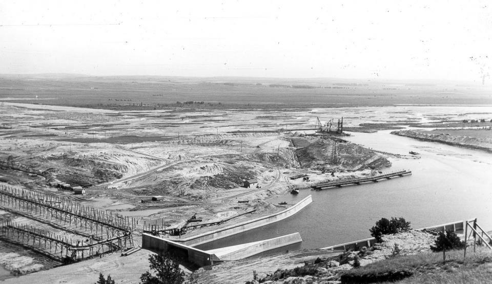 A view of the east side of Kingsley Dam while workers construct the skeleton of the dam.