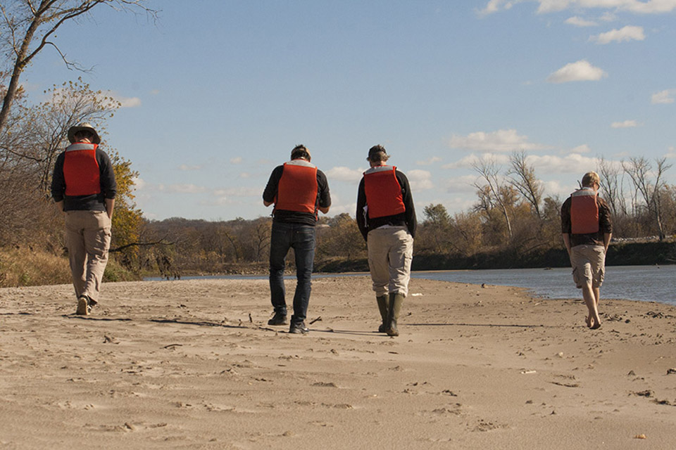 (From left to right) Twidwell, Angeler, Allen and Bieber walk down a wet sand bar to search for otter tracks.
