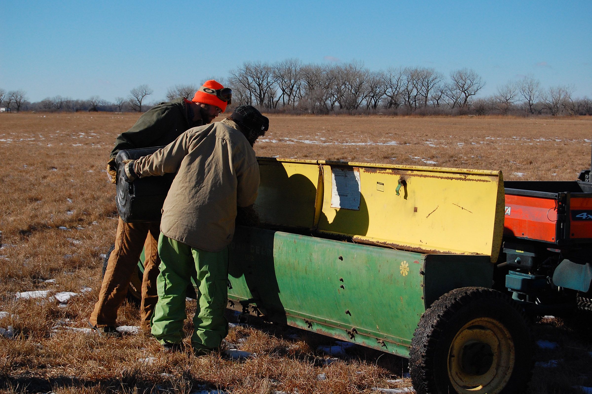 TNC fellows Jasmine Cutter and Dillon Blankenship load the mixed seed into the spreader. (Ariana Brocious)