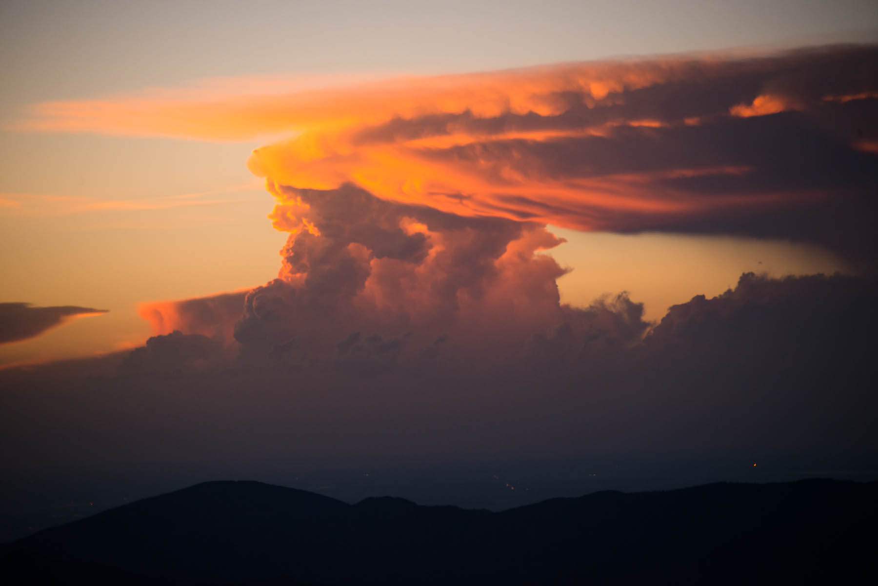 In early summer, a massive thunderhead builds over the eastern plains of Colorado at sunrise.