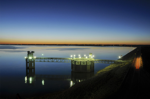 Lights from the Morning Glory Spillway glow in the evening twilight along the dam at Lake McConaughy. (Michael Farrell)