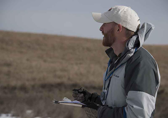 Ryan Joe makes notes of all the habitat characterisitics for the whooping crane stopover study. (Ariana Brocious)