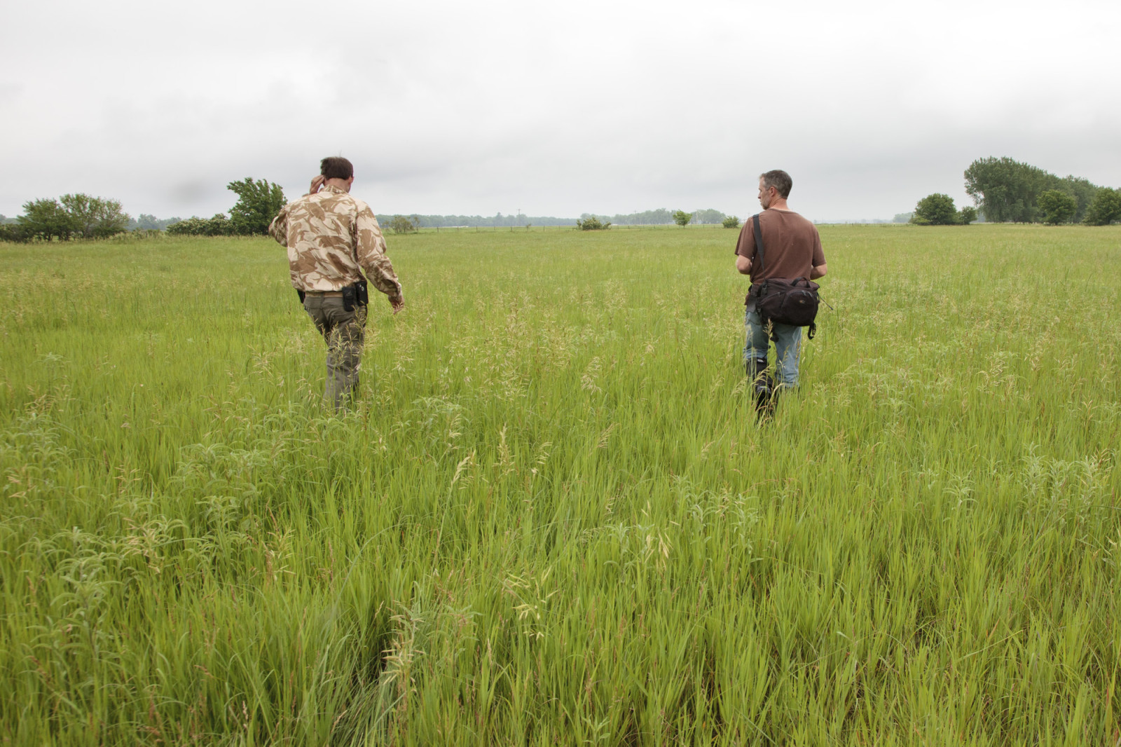 Chris Helzer (right) and Nelson Winkel (Land Manager of the Platte River Prairies, left) discuss management strategies while surveying a prairie. (Evan Barrientos)